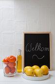 Zitrusfrüchte, Ölflasche und Willkommen-Tafel vor weißer Fliesenwand in der Küche