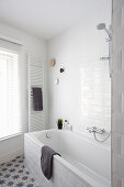 Bathtub, towel rail and window in white bathroom