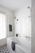 Weißes Badezimmer mit Badwanne, Handtuchtrockner und Fenster