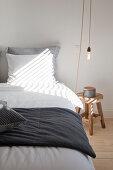 Doppelbett, Hocker als Nachttisch und Pendelleuchte im Schlafzimmer