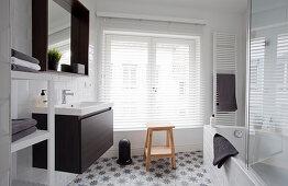 Waschbecken, Spiegel, Fenster mit Jalousie Handtuchtrockner und Badewanne im Badezimmer