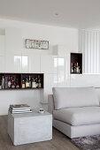 Würfelförmiger Beistelltisch im Betonlook vor moderner Wohnwand