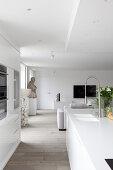 Blick von der offenen Küche in das moderne Wohnzimmer in Weiß