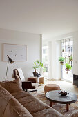 Pale brown couch, coffee table, pouffe and swivel chair in living room with house plants suspended in large window