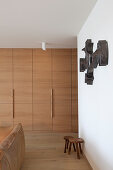 Floor-to-ceiling fitted wardrobes, wooden stools, sculpture on wall and leather couch in living room