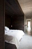 Bett in einer mit dunklem Holz verkleideten Nische im langen Flur