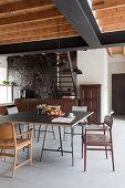 Verschiedene Stühle um den Esstisch in offener Küche im Industriestil