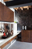 Designer kitchen with rust-effect metal cabinets and concrete floor