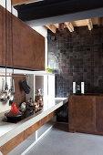 Küche im Designerstil mit rostigen Metallfronten und Betonboden