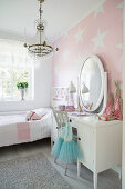 White dressing table with mirror in girl's bedroom with star-patterned wallpaper