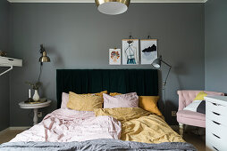 Pastel accessories in bedroom with grey walls