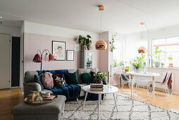 Grey sofa and dining table in living room with pink wall