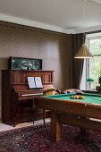 Piano and pool table in masculine living room