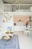 White couch, white dining table and kitchen below bedroom gallery in open-plan interior