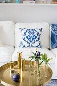 Glass vases and candles on round tray table in front of white couch with white and blue scatter cushions