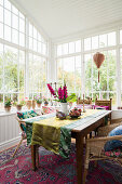 Runner and flowers on dining table with rattan armchairs and potted plants in conservatory