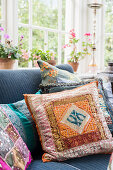 Colourful scatter cushions on sofa in conservatory