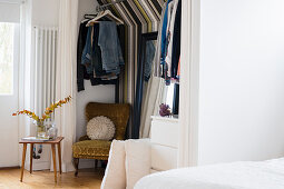 Walk-in wardrobe with striped wallpaper in bedroom