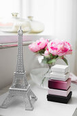 Miniature Eiffel Tower, boxes and roses in spherical vase on bedside table