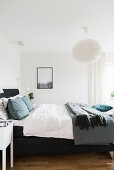 Double bed in bedroom with white walls