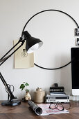 Black table lamp on desk and round black frame on wall used as pinboard