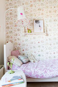 Bed against floral wallpaper in vintage-style child's bedroom