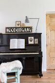 Old sign and anglepoise lamp on top of black piano