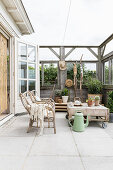 Pallet table and wicker sofa on vintage-style veranda with half-open walls
