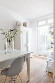 White dining table and classic chairs on wooden floor in front of white cupboard next to terrace doors