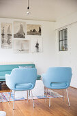 Two blue armchair in front of pictures of sailing boats on wall