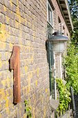 Hausnummer 1 aus rostigem Metall an einer Backsteinwand