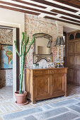 Cactus and old sideboard against brick wall in hallway