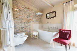 Curved bathtub and stone wall in elegant bathroom