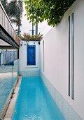 Langer schmaler Pool und eine blaue alte Tür