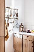 Hakenleiste für Kochutensilien in der Küche mit Holzfronten