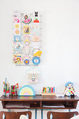 Vintage school bench below postcard rack on white wall