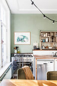 Green wall, gas cooker and vintage fridge in kitchen
