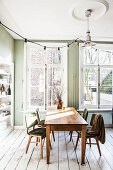 Dining table and chairs in front of large windows in dining room with green walls and white wooden floor