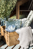 Crockery, cushions and roll of wallpaper in wooden crate