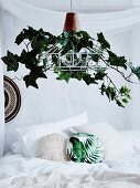 Lampshade decorated with artificial ivy over the bed