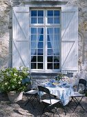 Set garden table below lattice window with shutters