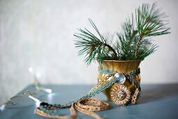 Brocade ribbons tied around gilt vase of fir branches