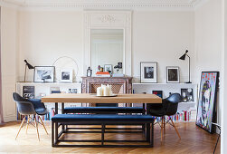 Modern dining table and upholstered benches in front of open fireplace