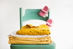 Stacked linen and hand-made felt butterflies on green chair