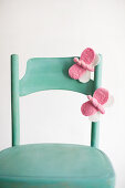 Hand-made, pink, felt butterflies on green chair