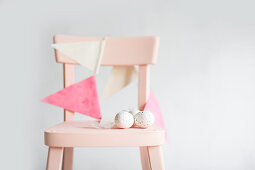 Bunting and speckled eggs on chair