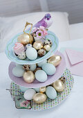 Easter eggs and bird figurine on cake stand
