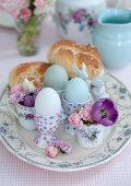 Eierbecher, Tassen mit Blüten und Hefegebäck auf Ostertisch