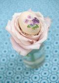 Ei mit Glitzerblüten in Rosenblätterneingebettet