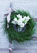 Wreath of bilberry twigs and white spring flowers on a ladder